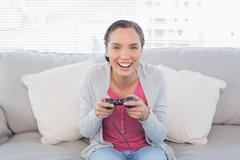Stock Photo of Smiling woman sitting on sofa playing video games