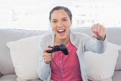 Woman playing video games on sofa and winning Stock Photos