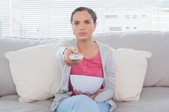 Unsmiling woman sitting on sofa wathing televion and holding popcorn Stock Photos