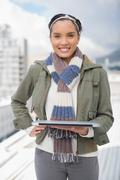 Portait of smiling woman standing outside and holding laptop - stock photo