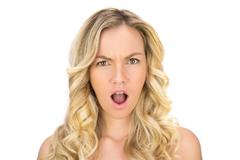 Shocked curly haired blonde posing Stock Photos