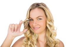 Smiling curly haired blonde holding eyelash curler - stock photo