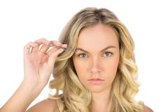 Serious curly haired blonde using tweezers Stock Photos
