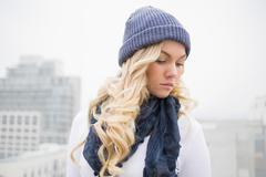 Stock Photo of Thoughtful blonde in winter clothes posing outdoors