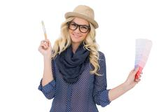 Cheerful trendy blonde with classy glasses holding color chart - stock photo
