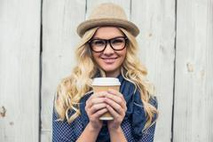 Stock Photo of Cheerful fashionable blonde holding coffee outdoors