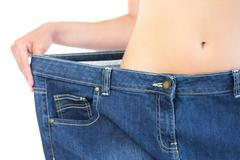 Extreme close up of confident slender blonde wearing too big trousers Stock Photos