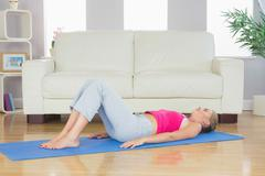 Sporty tired blonde lying on exercise mat - stock photo