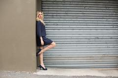 Serious gorgeous blonde wearing classy dress posing outdoors Stock Photos