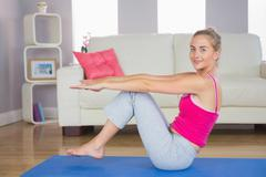 Sporty smiling blonde doing core exercise - stock photo