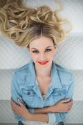 Smiling blonde wearing denim clothes lying on stairs Stock Photos