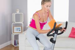 Sporty unsmiling blonde training on exercise bike reading a book - stock photo