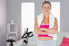 Sporty smiling blonde standing cross armed - stock photo