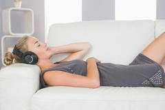 Stock Photo of Casual calm blonde lying on couch listening to music