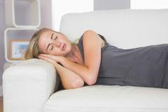 Stock Photo of Casual calm blonde lying on couch sleeping