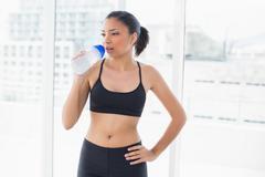 Charming dark haired model in sportswear drinking water Stock Photos