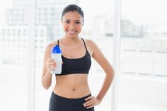 Content dark haired model in sportswear drinking water - stock photo