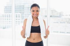 Assertive dark haired model in sportswear giving thumbs up - stock photo
