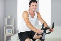 Stock Photo of Smiling sporty man exercising on bike and listening to music