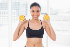 Beautiful dark haired model in sportswear holding orange halves - stock photo