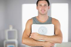 Stock Photo of Sporty smiling man holding a scale
