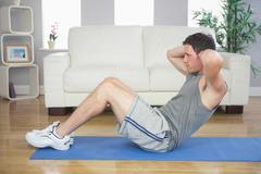 Fit handsome man doing sit ups - stock photo