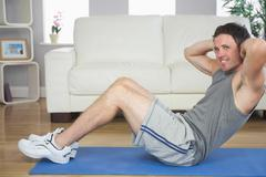 Handsome sporty man doing sit ups looking at camera - stock photo