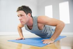 Attractive sporty man doing push ups on blue mat - stock photo