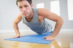 Attractive sporty man doing push ups on blue mat looking at camera - stock photo