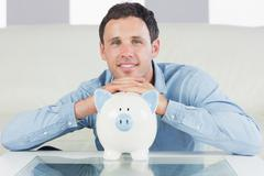 Stock Photo of Cheerful casual man resting head on piggy bank
