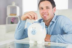 Stock Photo of Handsome casual man putting coin in piggy bank smiling at camera