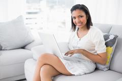 Attractive young dark haired woman in white clothes using a laptop - stock photo