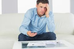 Stock Photo of Upset casual man using calculator and looking at camera paying bills