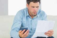 Serious casual man holding calculator paying bills looking at document - stock photo