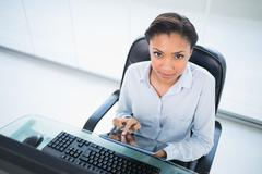 Stock Photo of Serious young dark haired businesswoman using a tablet pc