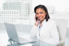 Stylish young dark haired businesswoman making a phone call Stock Photos