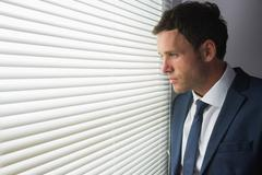 Serious handsome businessman looking out of window Stock Photos