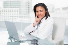 Dreamy young dark haired businesswoman using a laptop - stock photo