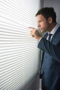 Unsmiling handsome businessman looking through roller blind - stock photo