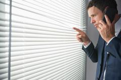 Stock Photo of Unsmiling handsome businessman looking through roller blind phoning