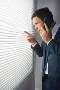 Serious handsome businessman looking through roller blind phoning - stock photo