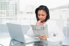 Concentrated young dark haired businesswoman reading a document - stock photo