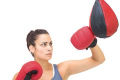 Serious sporty brunette training with punching bag - stock photo