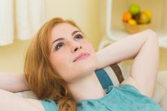 Stock Photo of Calm redhead lying on the couch looking up