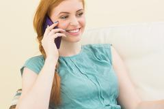 Stock Photo of Smiling redhead sitting on the couch making a call