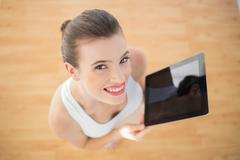 Delighted fit brown haired model in sportswear holding a tablet pc - stock photo