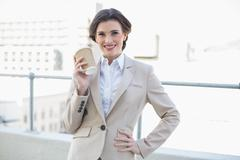 Joyful stylish brown haired businesswoman holding a coffee cup Stock Photos