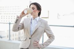Peaceful stylish brown haired businesswoman drinking coffee Stock Photos