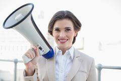 Pleased stylish brown haired businesswoman holding a megaphone - stock photo