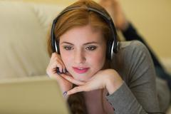 Cute redhead lying on the sofa with her laptop listening to music - stock photo